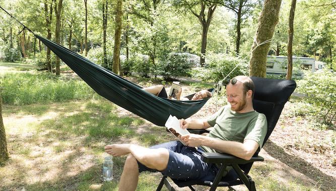 stel geniet op Natuurkampeerterrein van lezen in een hangmat