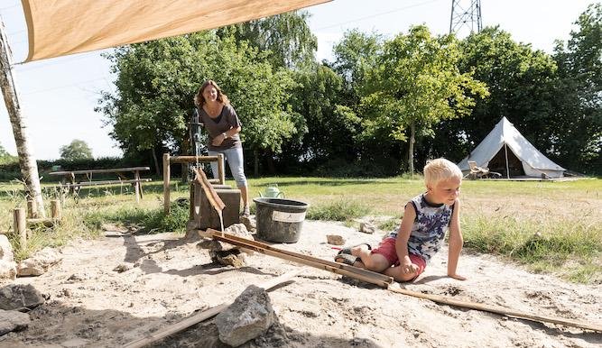kind speelt bij waterpomp in het zand op een Natuurkampeerterrein